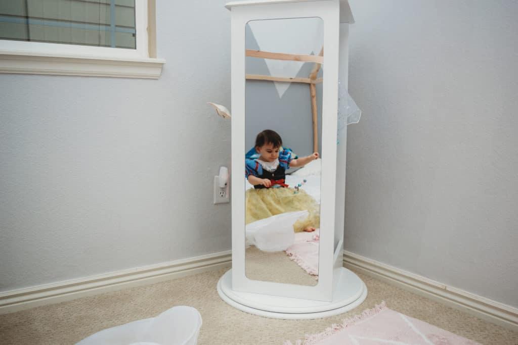 mirror image of toddler girl in princess dress