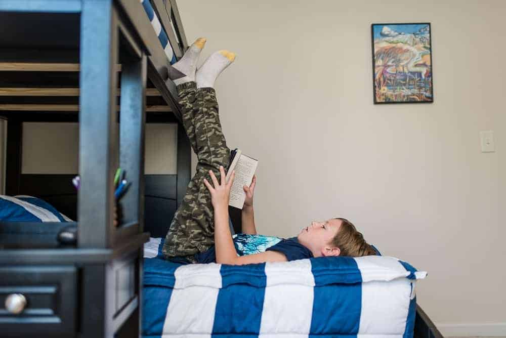 boy reading a book on bunk beds
