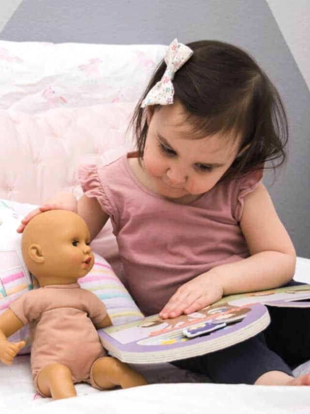 toddler reading book to baby doll